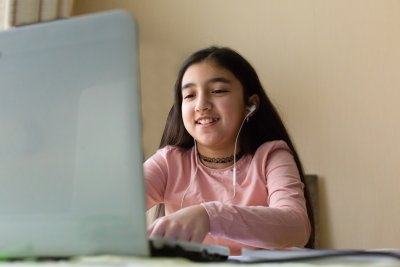 Young girl sitting at the dining table with laptop at home schooling, online virtual classroom video conference, distant education. Active participation at the lesson with earphones, doing homework.